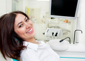 dark haired woman smiling in dental chair