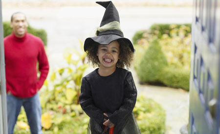 Girl in witch costume trick or treats