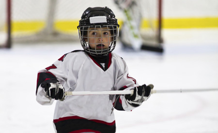 A child plays hockey while wearing a mouthguard