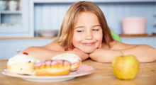 Girl looking at donuts and an apple