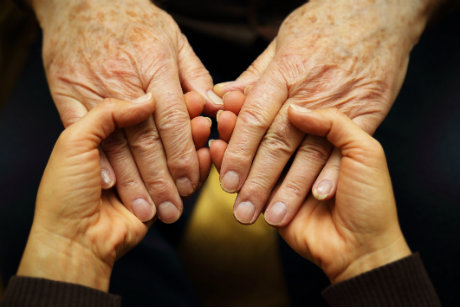 Holding hands with elderly loved one
