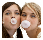 Two girls blowing bubbles with chewing gum