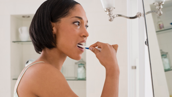 young woman brushing her teeth and looking at her own reflection in the mirror