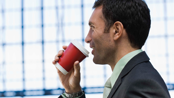 man drinking coffee in a to-go cup