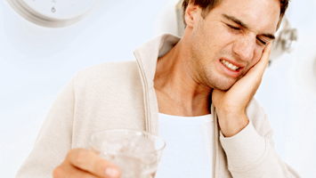 Young man grimacing in pain after drinking cold water