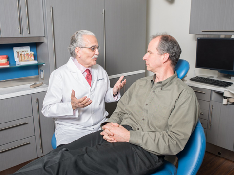 Man discussing oral cancer screening with his dentist