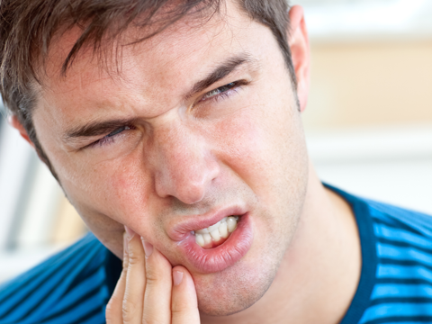 Young man grimacing with a toothache