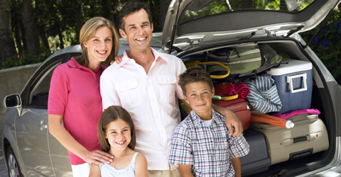 Family leaving on vacation with car packed for road trip.