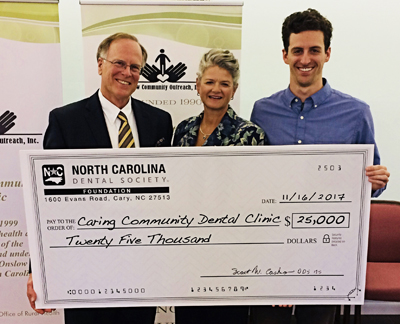 Photo of Drs. James and Virginia Wilson, with their son Hunter, posing with a donation check