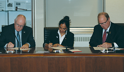 Photo of Drs. MacNeil and Crowley signing the agreement