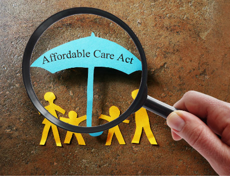 paper cut out family under an umbrella with words affordable care act