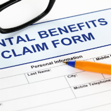 A dental benefits claim form with a pen