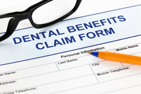 Dental benefits claim form with pen and pair of glasses