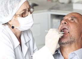 Dentist examines man