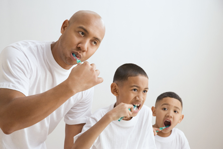 father and sons brush their teeth together
