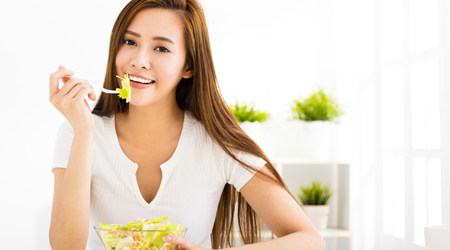 Woman eating salad while showing healthy smile