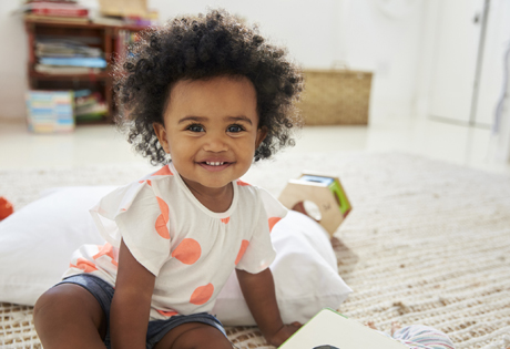 Toddler girl smiling in a playroom