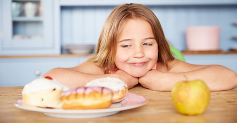 Girl choosing between healthy snack and unhealthy snack