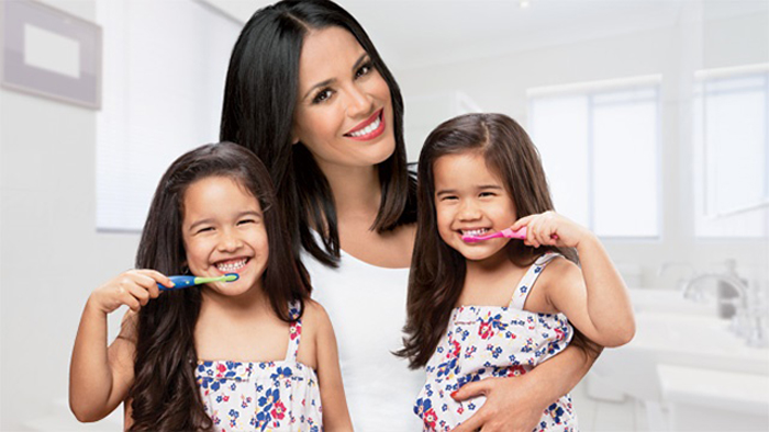 Mom and daughters brushing teeth