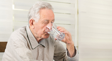 Elderly man drinking water