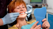 Woman examines smile in dentist's office