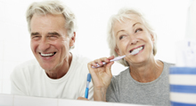 Older couple brushing teeth