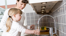 Mother and daughter filling water glass in sink