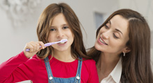Girl brushes teeth as mom looks on