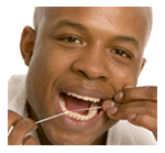 man using dental floss on lower teeth