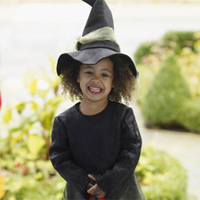 Young girl dressed as a witch trick-or-treating