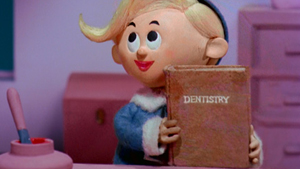 Hermey the Elf holding a book about dentistry