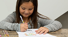 photo of girl writing at desk