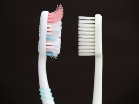 Toothbrush that needs replacing next to a new toothbrush