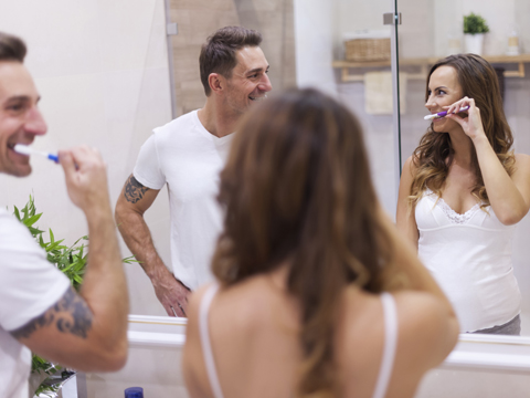 Pregnant woman and partner brush their teeth together