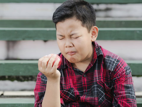 Boy winces while eating an apple