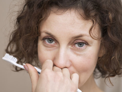 Woman hiding her smile holding a toothbrush
