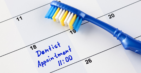 Toothbrush on a calendar with reminder to make dental appointment