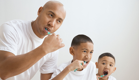 father and sons brushing their teeth