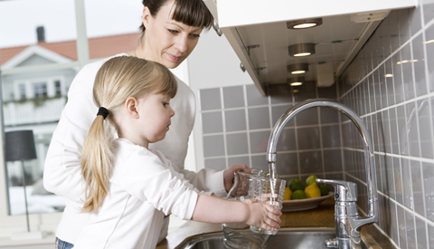 Mother and daughter filling glass with tap water