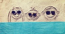 3 faces smiling in sand